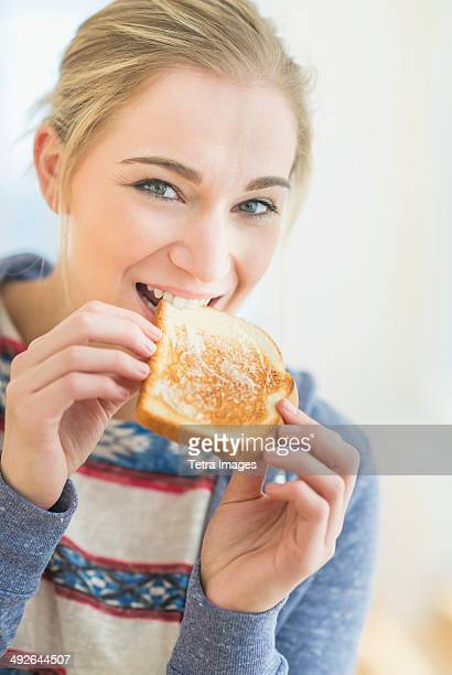 Woman eating toast, Jersey City, New Jersey, USA