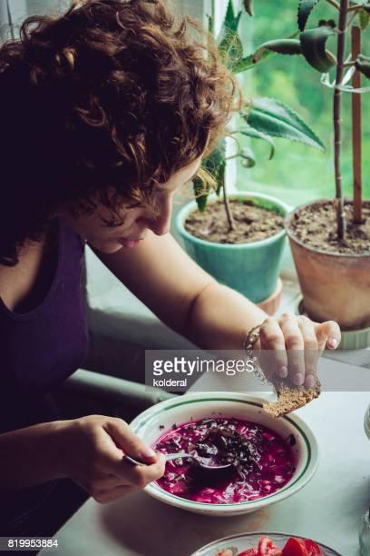 Woman eating traditional Ukrainian borscht soup at home kitchen