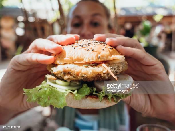 vrouw die veganistische hamburger in koel café eet - vegetarisch gerecht stockfoto's en -beelden