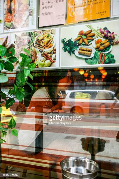woman eating with chopsticks in window - merten snijders stock pictures, royalty-free photos & images