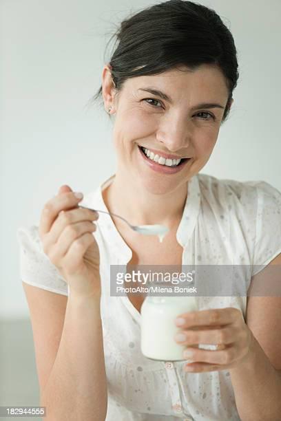 Woman eating yogurt, portrait