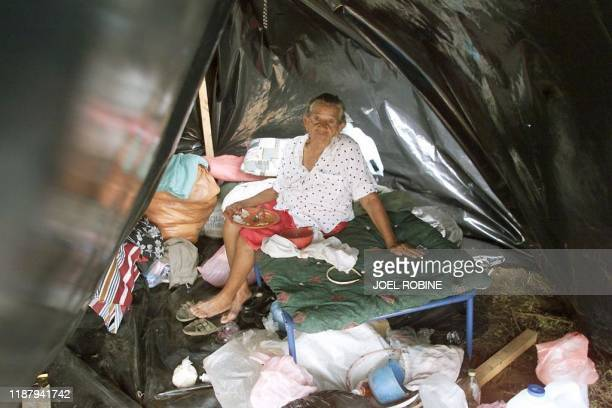 A woman eats a meal 09 November in a tent in the New Life Quarter a camp of plastic sheeting and shacks installed at Ciudad Sandino 15 kilometers...