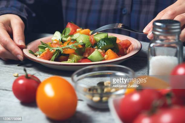 a woman eats a vegetarian vegetable salad. - tomato stock pictures, royalty-free photos & images