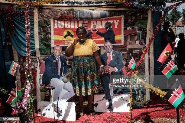 TOPSHOT A woman eats an ice candy before posing for a photograph between posters of Kenya's President Uhuru Kenyatta and VicePresident William Ruto...