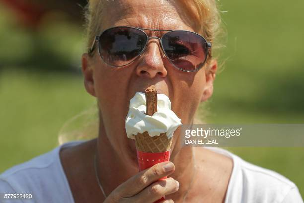 A woman eats an ice cream in front of the London Eye during a hot and sunny day in central London on July 20 2016 / AFP / DANIEL LEALOLIVAS