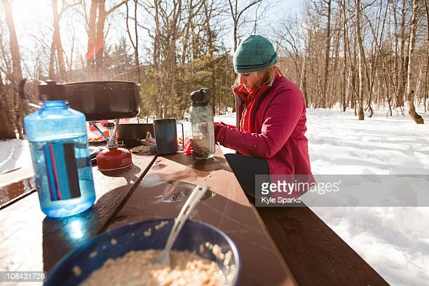 A woman eats breakfast while camping off the Kangamangus Highway near Conway, New Hampshire.