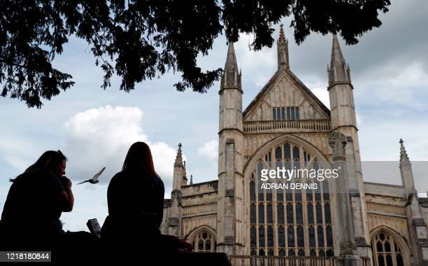 A woman eats her lunch as a pigeon flies past in the grounds of Winchester Cathedral in Winchester southern England on June 7 2020 The UK government...