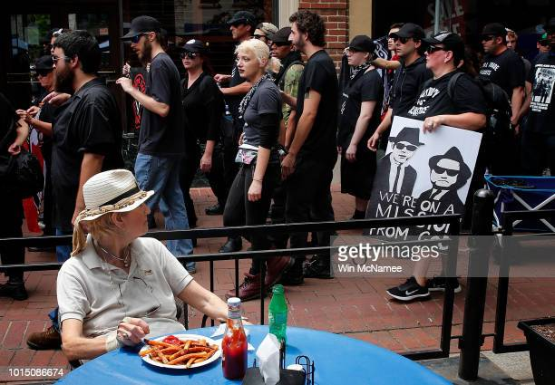 A woman eats lunch as a group of protesters known as 'Antifa' or antifascists march through the downtown mall area near the site of a makeshift...