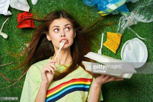 a woman eats takeaway food in an environment with garbage and waste plastic and paper - flick stock pictures, royalty-free photos & images