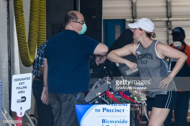 A woman elbow bump with the election worker ahead of casting her vote during the Florida primary election at Miami Beach Fire Rescue Station 3 in...