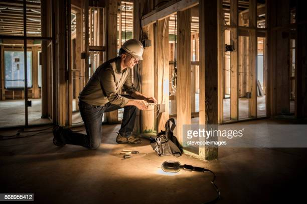 Woman electrician at home construction site.