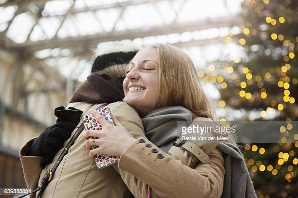 Woman embraces her friend at railroad station, christmas tree in background.