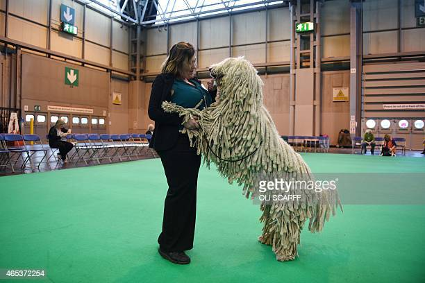 A woman embraces her Komondor dog before it is judged on the second day of the Crufts dog show at the National Exhibition Centre in Birmingham...