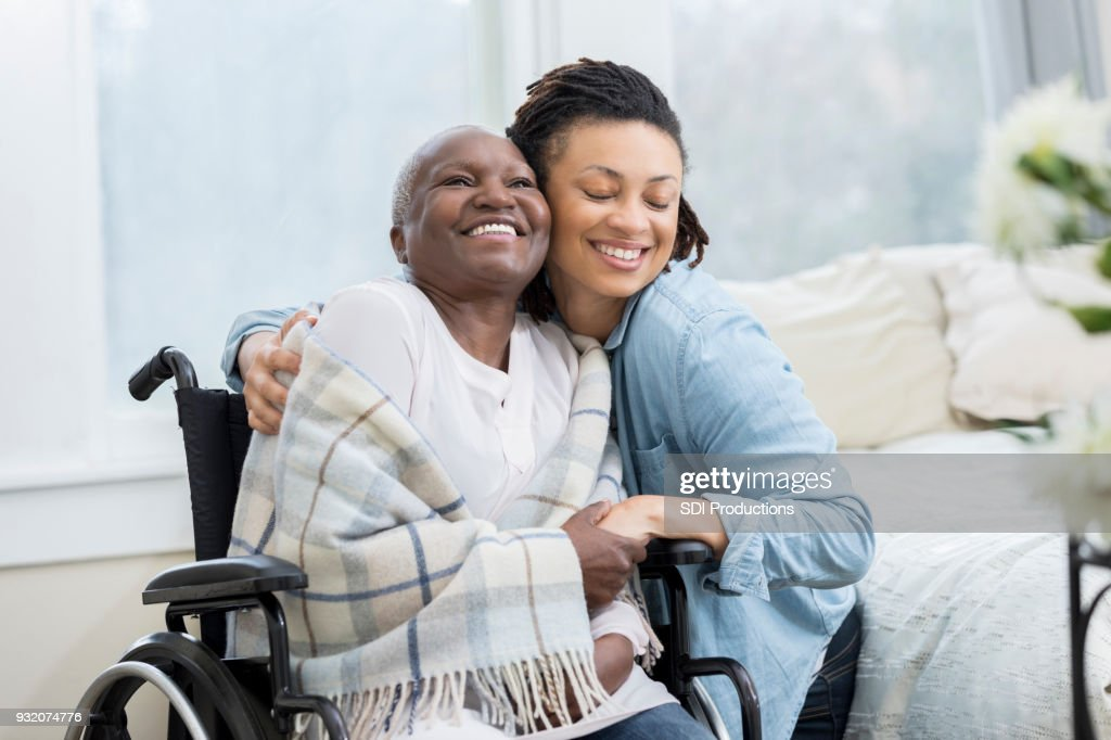 Woman embraces her wheelchair-bound mother : Stock Photo