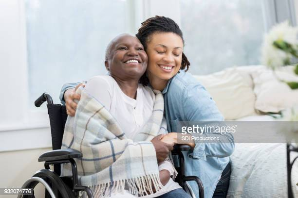 woman embraces her wheelchair-bound mother - cancer illness stock pictures, royalty-free photos & images