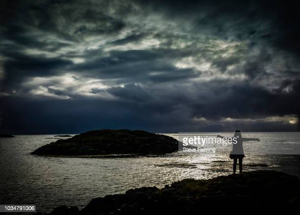 A woman embraces the storm overlooking the Atlantic Ocean at Andenes, Northern Norway.