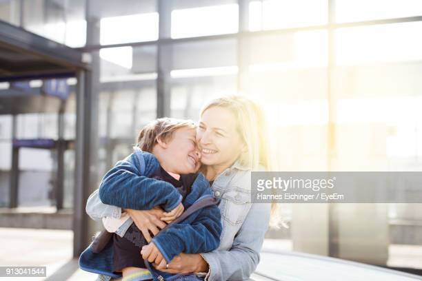 Woman Embracing Boy While Sitting At Home