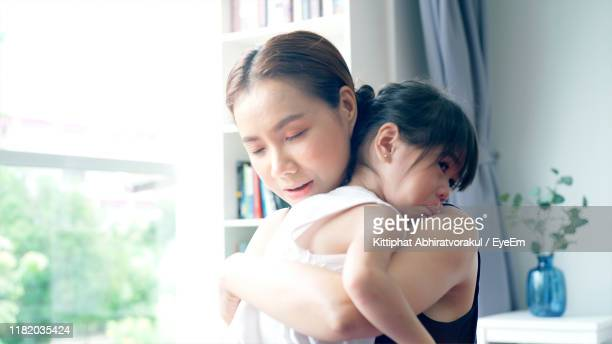 woman embracing daughter at home - compassionate eye stock pictures, royalty-free photos & images