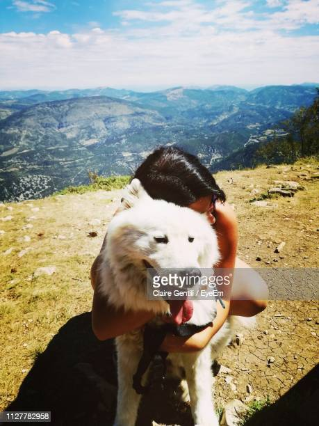 Woman Embracing Dog On Landscape