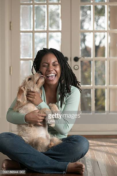 Woman embracing dog sitting on floor, dog licking woman's face