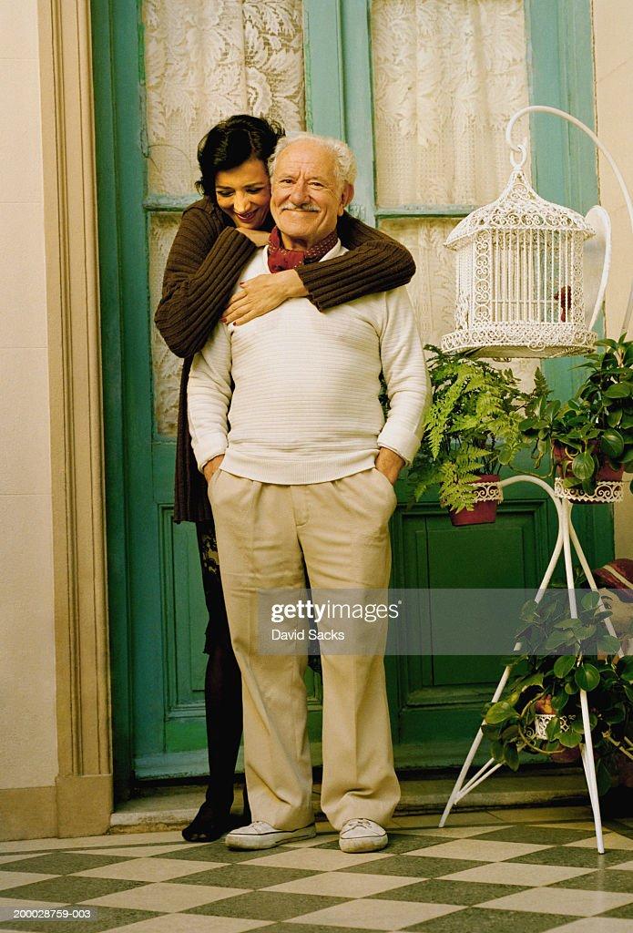 Woman embracing elderly man : Stock Photo