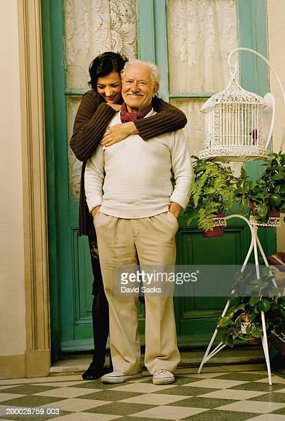 Woman embracing elderly man