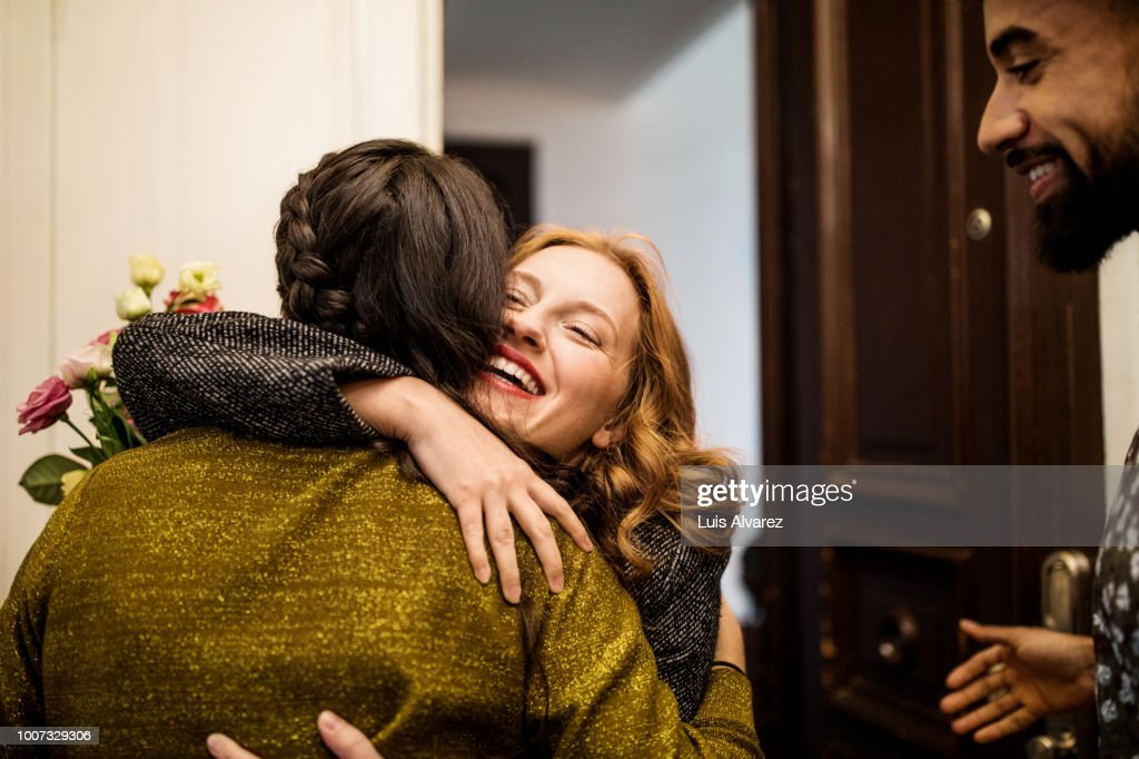 Woman embracing friend during visit for dinner party : Stock Photo