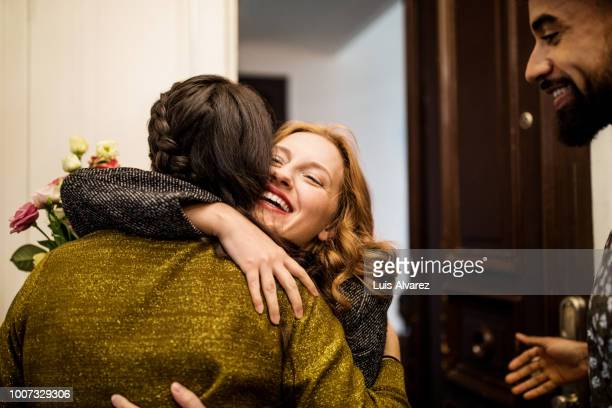 woman embracing friend during visit for dinner party - ankunft stock-fotos und bilder