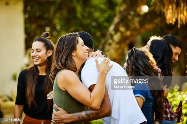 woman embracing friend in backyard during visit - aanhankelijk stockfoto's en -beelden