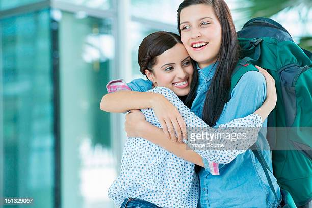 Woman embracing friend with backpack
