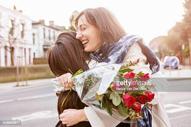 Woman embracing girlfriend with bunch of roses.