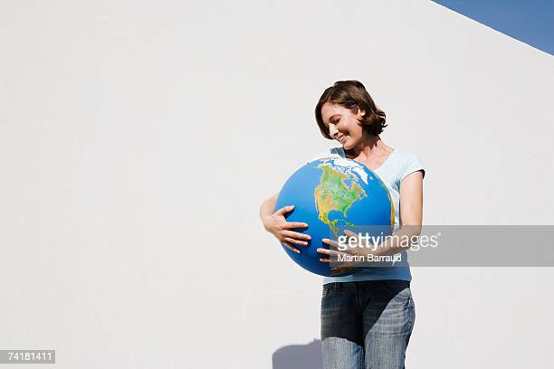 Woman embracing globe and smiling outdoors