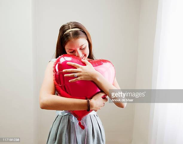 Woman embracing heart shaped balloon