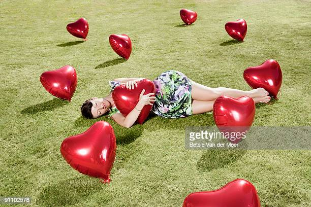 woman embracing heartshaped balloon in grass.