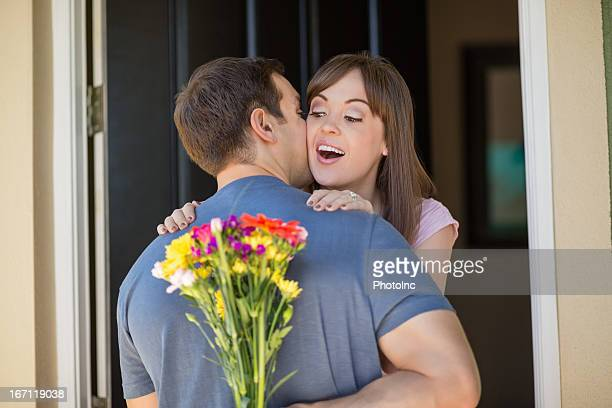 Woman Embracing Man As He Hides Flowers