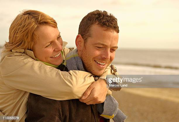 Woman embracing man from behind on beach