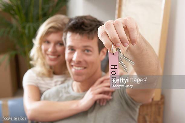 Woman embracing man holding up house keys, portrait (focus on keys)