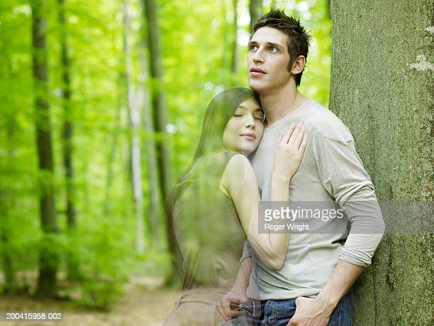 Woman embracing man leaning against tree in forest (digital composite)