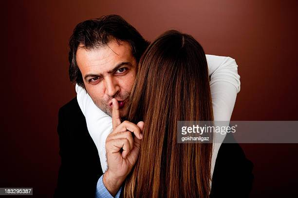 Woman embracing man making a shushing gesture