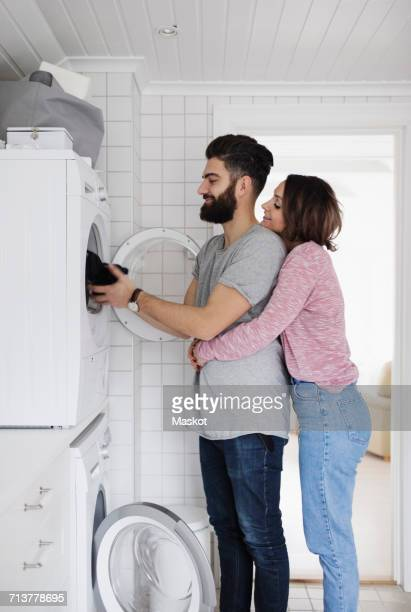 Woman embracing man while loading clothes in washing machine at home
