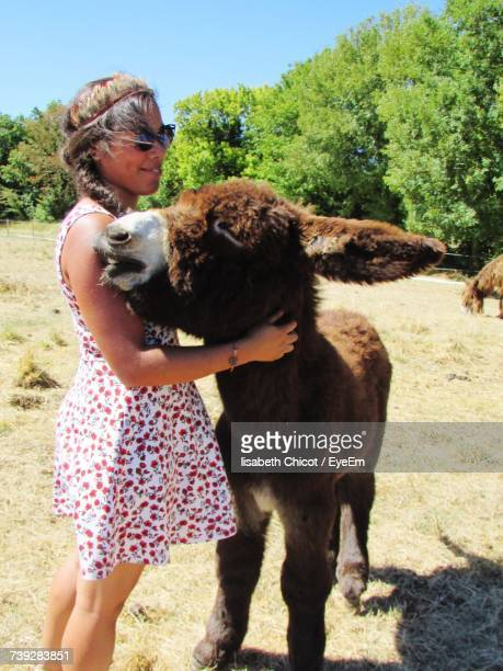 Woman Embracing Poitou Donkey While Standing On Field On Sunny Day
