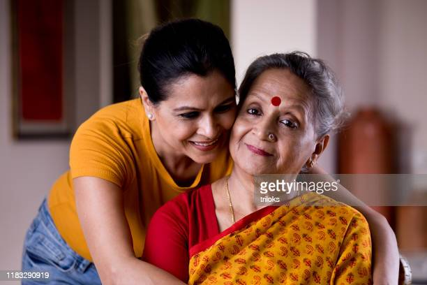 woman embracing senior mother from behind - indian culture stock pictures, royalty-free photos & images