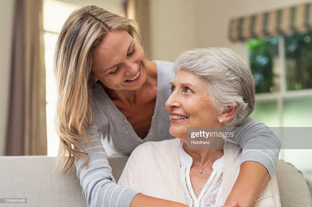 Vrouw omhelst senior moeder : Stockfoto