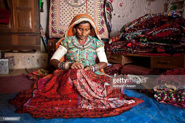 Woman embroidering fabric. inside house.