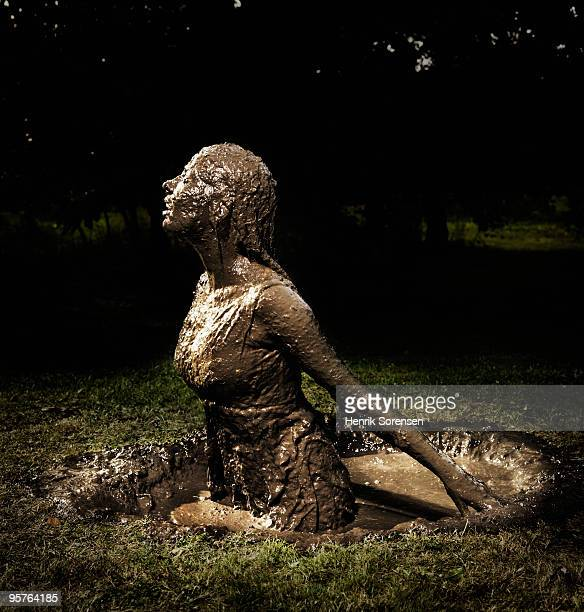 Woman emerging from a mud hole