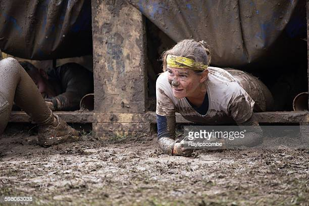 Woman emerging from a muddy hole