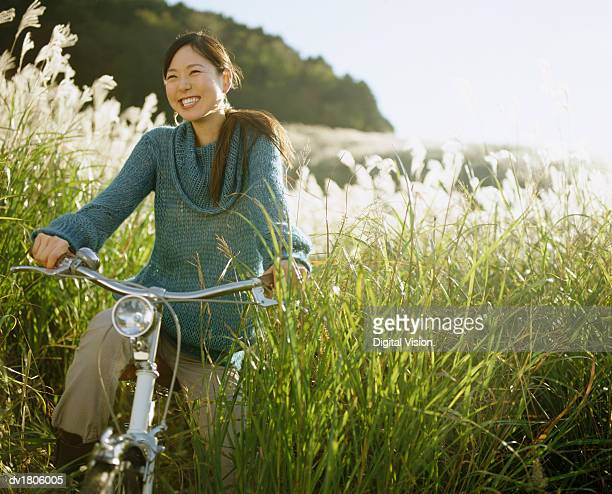 Woman Emerging from Long Grass on a Bicycle