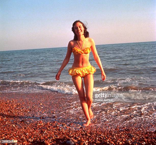 A woman emerging from the sea wearing a yellow bikini