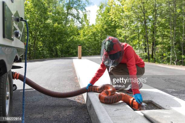 woman emptying rv sewer after camping - sewer stock pictures, royalty-free photos & images