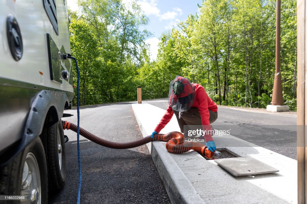 Woman Emptying RV Sewer After Camping : Stock Photo